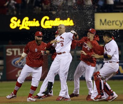 Cardinals' Carlos Beltran (3) and teammates party following his game-winning hit in the 13th inning after midnight. (Associated Press)