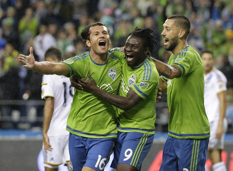 Seattle Sounders' Nelson Valdez, left, celebrates with teammates Obafemi Martins, center, and Clint Dempsey, right, after Valdez scored a goal against the Los Angeles Galaxy in the first half of an MLS soccer western conference knockout round playoff match, Wednesday, Oct. 28, 2015, in Seattle. (AP Photo/Ted S. Warren) ORG XMIT: WATW106 (Ted S. Warren / AP)