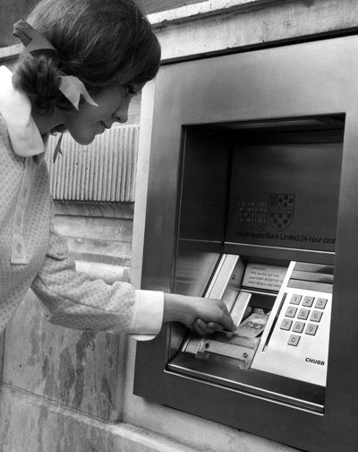 A woman puts her computer punch card into the slot of an automated teller machine outside a bank in central London in January 1968.The first ATM was installed in London in 1967, with John Shepherd-Barron being credited with inventing the machine. (Associated Press)