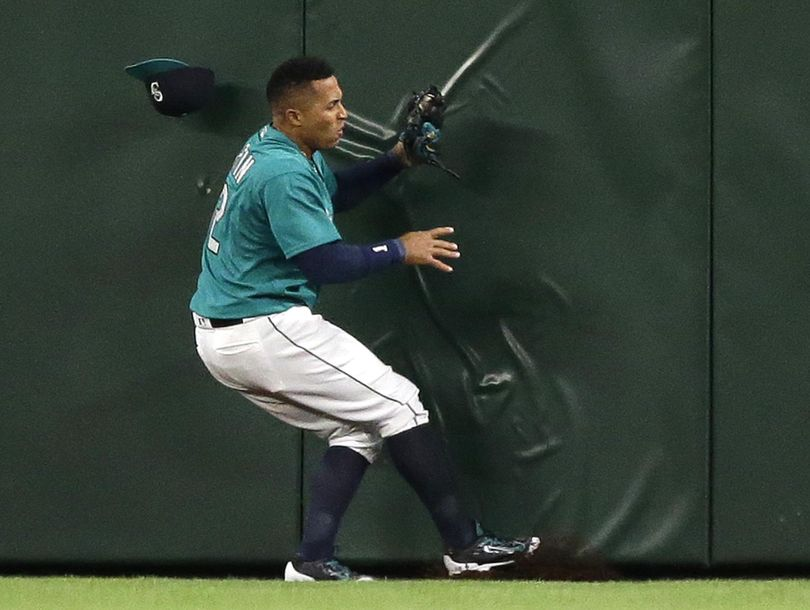 Mariners center fielder Leonys Martin loses his cap but holds on to the ball as he collides with the outfield wall after he caught a fly ball hit by Kansas City Royals' Salvador Perez for the final out in Friday's night's game. The Mariners won 1-0. (Ted S. Warren / Associated Press)