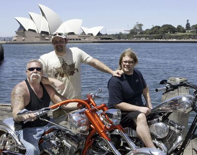 """In this Feb. 15, 2007 photo, Paul Teutul Sr. left, and sons Paul Jr. center, and Mikey from the popular reality television show """"American Chopper"""" try out an Australian-made chopper during a visit to Sydney, Australia. (Rob Griffith / Associated Press)"""