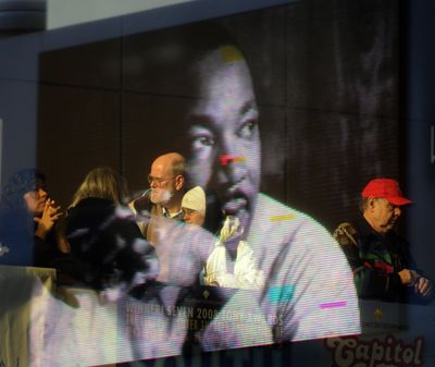 An image of  the Rev. Martin Luther King Jr. from the marquee is reflected onto the glass of the INB Performing Arts Center,  where more than  1,000 people gathered  before the  Unity March through downtown Spokane on Monday.  (J. BART RAYNIAK)