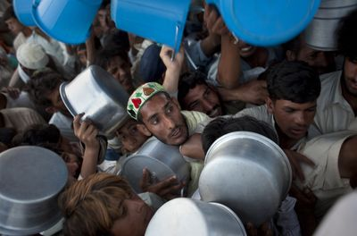 Displaced men and boys struggle to get their daily ration during a food distribution at the Chota Lahore refugee camp in northwest Pakistan on Saturday.  (Associated Press / The Spokesman-Review)