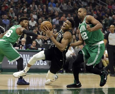 Bucks forward Giannis Antetokounmpo falls to the floor while defended by Boston Celtics' Al Horford, right, during the first half  Thursday, Feb. 21, 2019, in Milwaukee. (Aaron Gash / Associated Press)