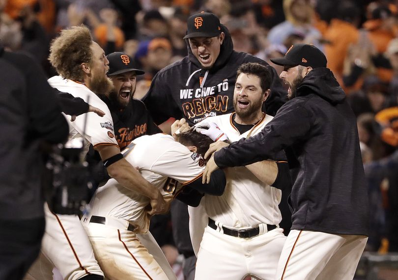 San Francisco's' Joe Panik, center bottom, is congratulated by teammates after hitting a double to score Brandon Crawford with the winning run in the bottom of the 13th, defeating the Cubs 6-5. (Marcio Jose Sanchez / Associated Press)