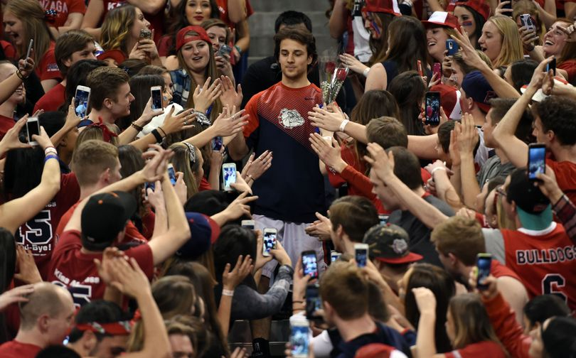 Senior, Gonzaga guard Kevin Pangos (4) makes his way through the Kennel Club student section after being introduced during Senior Night before the game with BYU, Sat., Feb. 28, 2015, in the McCarthey Athletic Center. (Colin Mulvany / The Spokesman-Review)