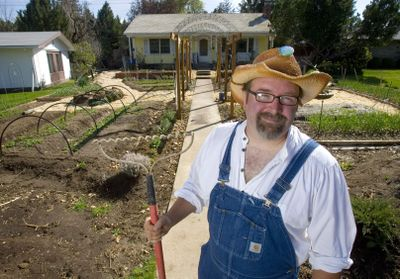 Bingo Barnes stands in the relandscaped front yard of his girlfriend's home in Boise. He converted the ever-so-common green grass and hedge into a functioning urban garden. He said it uses about the same amount of water, and he sells the produce. Barnes manages nine garden plots around the city. (Associated Press / The Spokesman-Review)