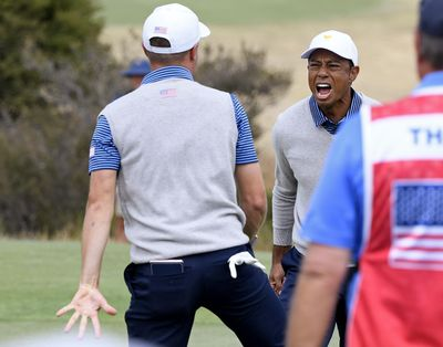 U.S. team player Justin Thomas, left, celebrates with his playing partner and captain, Tiger Woods, on the 18th green in their foursomes match during the President's Cup golf tournament at Royal Melbourne Golf Club in Melbourne, Friday, Dec. 13, 2019. (Andy Brownbill / AP)