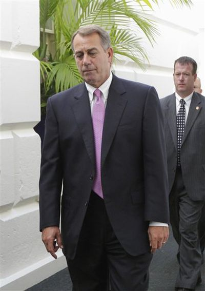 House Speaker John Boehner of Ohio walks through a basement corridor in the Capitol in Washington on Wednesday, after an afternoon caucus with House Republicans seeking an agreement on legislation to raise the nation's debt limit. (Associated Press)