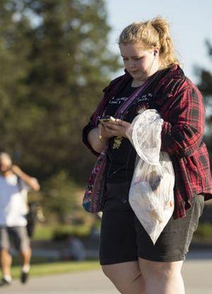 Alissa Bajramovic, of Spokane, plays 'Pokemon Go' as she picks up trash during a Pokemon Go community event Wednesday evening at McEuen Park. (Loren Benoit/Coeur d'Alene Press photo)