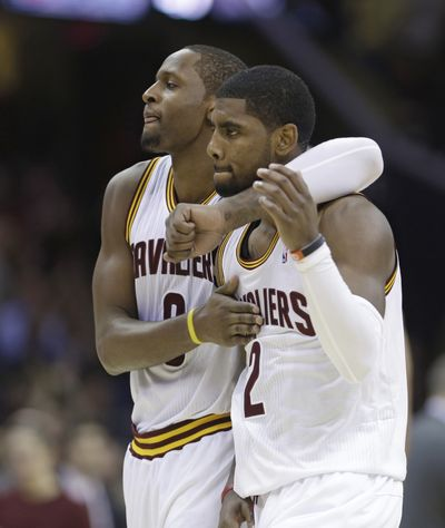 Cleveland's C.J. Miles, left, congratulates Kyrie Irving after Irving hit the game-winner during the second overtime against the 76ers. (Associated Press)