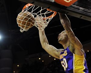 Lakers' Robert Sacre dunks the ball against the Rockets in his first career start on Tuesday night. (Associated Press)
