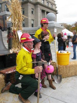 First Lady Lori Otter and Gov. Butch Otter, costumed as firefighters, distribute candy, books and toothbrushes to trick-or-treaters on the Statehouse steps on Oct. 31, 2013. (Betsy Russell)