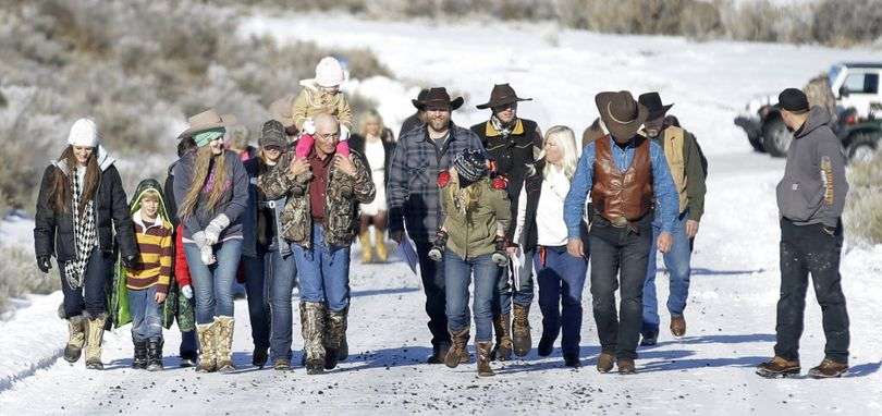 Ammon Bundy, center, one of the sons of Nevada rancher Cliven Bundy, arrives for a news conference with supporters at Malheur National Wildlife Refuge Friday, near Burns, Ore. Bundy the leader of a small, armed group occupying a national wildlife refuge in Oregon says the activists have no immediate plans to leave. Bundy spoke to reporters Friday, a day after meeting with a local sheriff who asked the group to go.(AP Photo/Rick Bowmer)