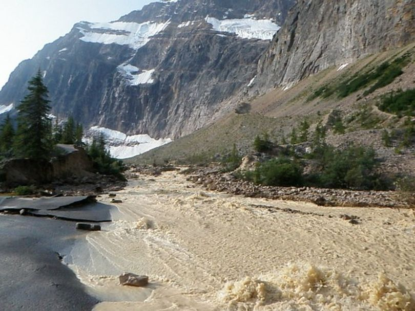 Water from Cavell Pond floods out to the Jasper National Park parking area after tons of ice from Ghost Glacier fell from the slopes of Mount Edith Cavell on Aug. 10, 2012. (Courtesy)