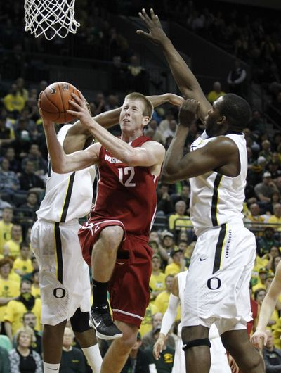 WSU's Brock Motum drives to the basket as Oregon's Tyrone Nared, left, and Olu Ashaolu close in. (Associated Press)