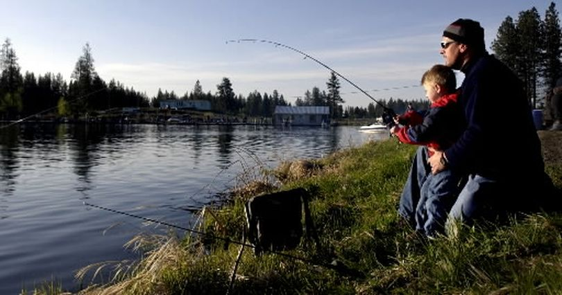 With one giant fish in the bag, three year old Jacksen (cq) and his dad Mike Kaiser try to land another trout at West Medical Lake early on the opening weekend of Washington's fishing season.  (FILE The Spokesman-Review)