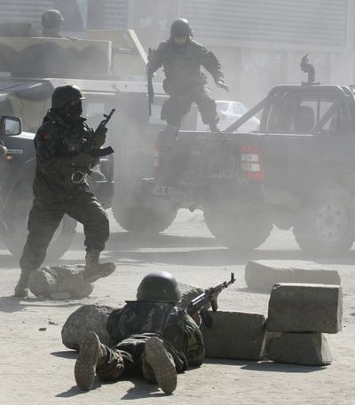 Afghan security forces run for the Afghan Justice Ministry following an attack in Kabul, Afghanistan on Wednesday.  The Taliban claimed responsibility for the attacks, which killed 20 and injured many.  (Associated Press / The Spokesman-Review)