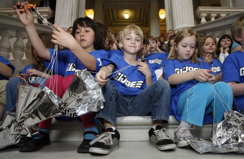 From left, Amanda Arroyo, Brady Moran, and Kiley O'Brien, first-graders at Cumberland Hills Elementary School, wrap up G.I. Joe figures that were launched with parachutes from the rotunda of the Rhode Island Statehouse in Providence, R.I., to open the 2010 International G.I. Joe Collectors' Convention, Friday, April 30, 2010. (Stew Milne / Fr56276 Ap)