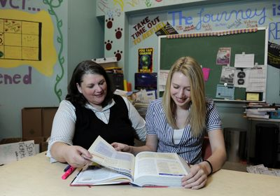 Jean Kliphuis, left, reviews a history textbook with her daughter, Katie, a senior at Walt Whitman High School, at the school n Huntington Station, N.Y.   (Associated Press / The Spokesman-Review)