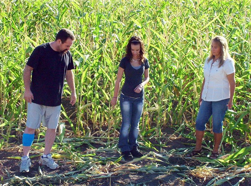 In this Monday, Oct. 3, 2011 photo provided by the Preston Citizen, from left, Michael Vaughn and his 17-year-old daughter Alexis talk with Sue Panter in a corn field where Panter on was attacked Friday, Sept. 30 by a mule deer near Franklin, Idaho. Panter was able to escape the attack after the Vaughns fought off the buck, grabbing the antlers and striking it with a hammer until it fled, state wildlife officials said. (Associated Press)
