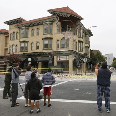 People photograph structural damage to a building which partially collapsed due to an earthquake today in Napa, Calif. A large earthquake caused significant damage and left at least three critically injured in California's northern Bay Area, igniting fires, injuring scores of people and knocking out power to tens of thousands.  (Ben Margot / Associated Press)