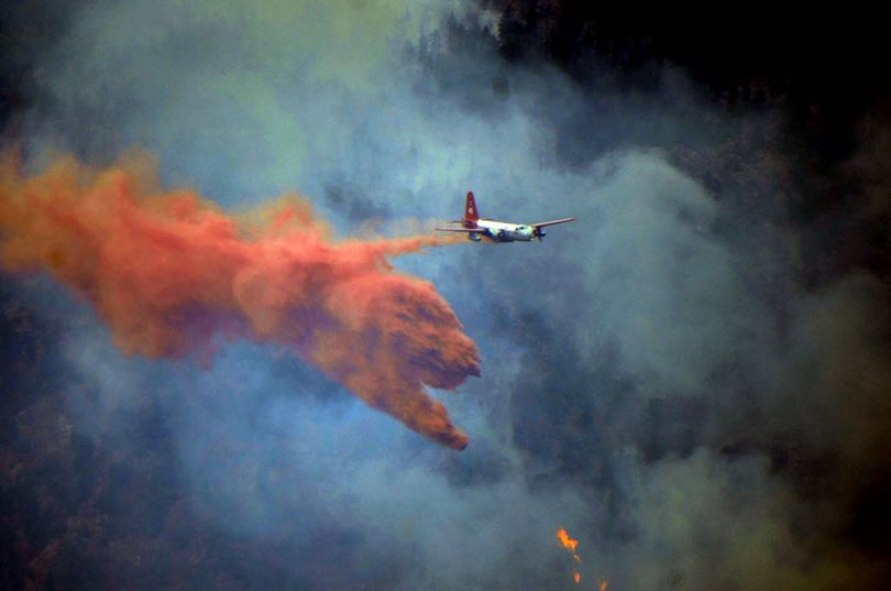 A plane drops fire retardant on a forest fire in Colorado. (Associated Press)