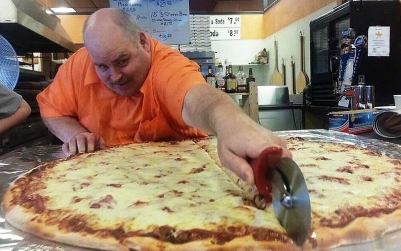 Nate's New York Pizza owner Glenn Gatherer sections off one of the restaurant's 36-inch pizzas. Nate's is open Wednesday through Sunday. (Courtesy photo via Coeur d'Alene Press)