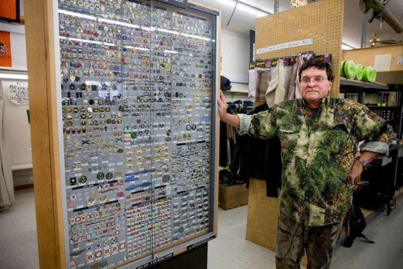 Army and Navy Outdoor owner Phil Motl poses next to a expansive collection of more than 10,000 pins from various divisions of the United States military that are for sale in the store. After investing thousands of dollars into the collection, he hasn't yet found a place for the pins for when the store closes in the coming months.