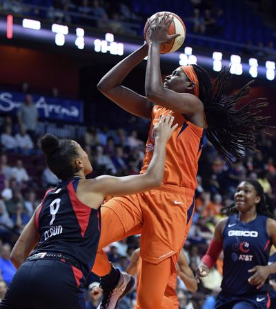 In this June 11, 2019 photo, Connecticut Sun center Jonquel Jones shoots over Washington Mystics guard Natasha Cloud during a WNBA basketball game in Uncasville, Conn. Connecticut has risen back to the top of the standings behind solid play from Jonquel Jones and Alyssa Thomas. (Sean D. Elliot / Day via AP)