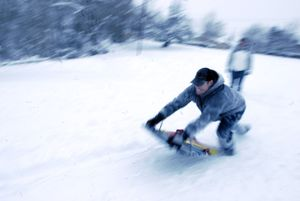 Chad Gilbert leaps onto his snow sled at the top of the sledding hill at Valley Mission Park Monday. He and his family were enjoying the fresh snow. (J. Rayniak / The Spokesman-Review)