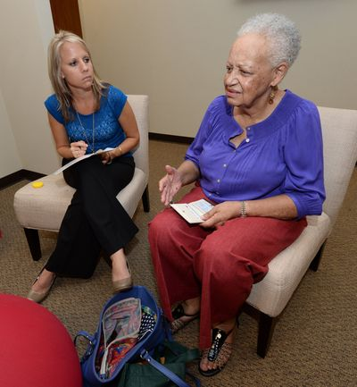 Kim Franklin, left, of the Alzheimer's Association, completes an application for a medic alert bracelet for Carol Moore at the association's office in Dunwoody, Ga., on Sept. 17. Moore has been diagnosed with early-onset Alzheimer's.