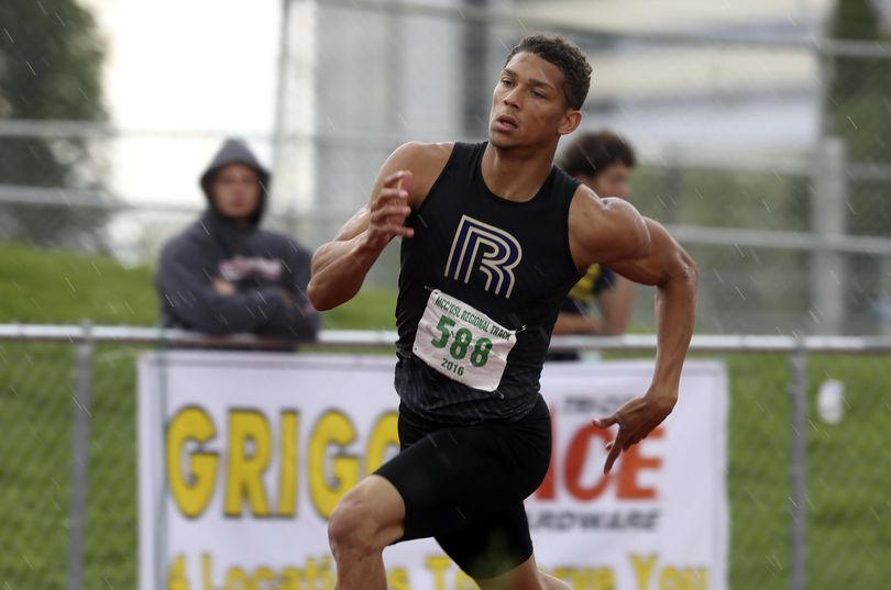 Rogers High School's Roberto Lopez runs through the rain Saturday during the regional track and field championships at Fran Rish Stadium in Richland. (Sarah Gordon / Tri-City Herald)