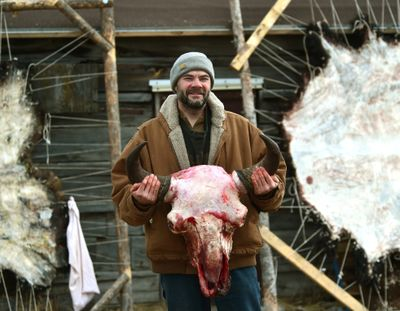 Jerry Moisin holds up a bison skull he skinned while taking part in the Buffalo Bridge Project near Gardiner, Mont., on Feb. 4, 2016. Since 2013, Buffalo Bridge has provided a unique service in the Gardiner Basin by scavenging bison hides, hooves, heads, rib cages, fat and internal organs from bison that hunters kill. From the scraps, the members make bison jerky and bone broth.  (Larry Mayer)