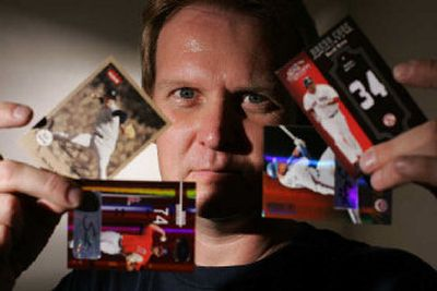 Mike Mittrick, who operates the 52 Mantle Card store in Brea, Calif., displays baseball trading cards in his shop last month. Faced with declining revenues over the past decade, the baseball card industry has been halved in a matter of months.  (Associated Press photos / The Spokesman-Review)