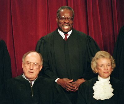 Associate Supreme Court Justice Clarence Thomas, center, laughs while posing with other members for a portrait at the court in Washington, D.C., Nov. 10, 1994. Seated in the front row are, Supreme Court Chief Justice William Rehnquist, left, and Associate Justice Sandra Day O'Connor. (J. SCOTT APPLEWHITE / Associated Press)