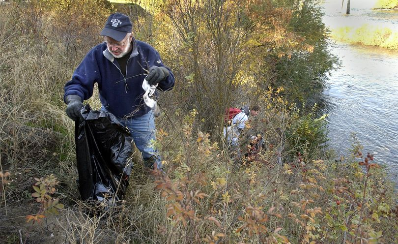Volunteers participate in the Spokane River Clean-Up in Peaceful Valley in 2003. (File)