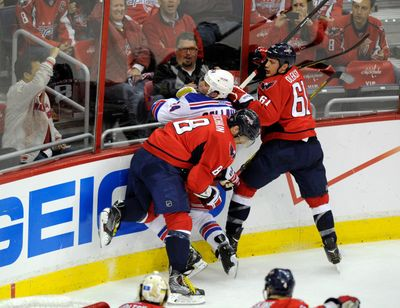 In this May 13, 2013, file photo, New York Rangers right wing Ryan Callahan (24) gets checked into the boards by Washington Capitals left wing Alex Ovechkin (8), from Russia, and Steve Oleksy during the second period of Game 7 of a first-round NHL Stanley Cup playoff hockey series in Washington. 2013 was the third year in a row the two teams met in the playoffs. (Nick Wass / Associated Press)