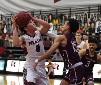 Whitworth guard Jake Holtz (0) eyes the basket as Puget Sound guard Jourdan Joseph (15) defends during the first half of a college basketball game, Friday, Feb. 12, 2021, at Whitworth University.  (Colin Mulvany/THE SPOKESMAN-REVIEW)