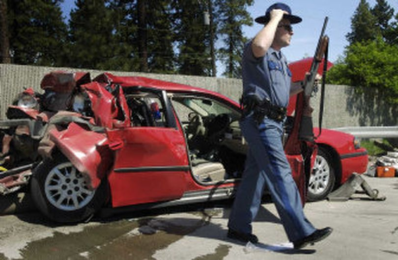 In this photo from May 2006, Washington State Patrol Sgt. Lee Slemp removes a shotgun from an unmarked patrol car that was rear-ended on I-90 near the Garden Springs exit.   (Colin Mulvany / The Spokesman-Review)