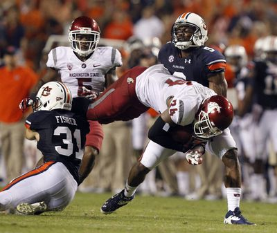 Cougars running back Teondray Caldwell dives for extra yardage over Auburn defensive back Trent Fisher during the second half. (Associated Press)
