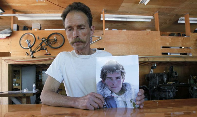 In this June 1, 2009 photo, Lou  Brown holds a photo of his son,  Sam Lindsay- Brown in his machine shop in Revelstoke, BC.  Sam Lindsay- Brown was a helicopter pilot and smuggler of drugs that he took from Canada in to the U.S. before being arrested in Ione, Wash., in February of 2009. He committed suicide while in custody. (AP Photo/Elaine Thompson) (Associated Press)