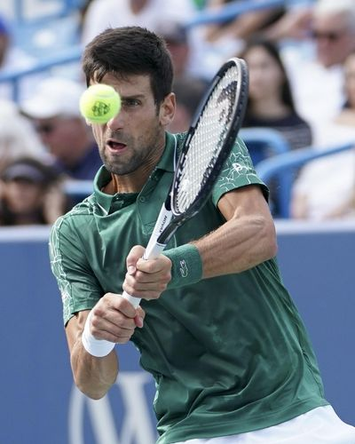 Novak Djokovic, of Serbia, returns Milos Raonic, of Canada, at the Western & Southern Open tennis tournament, Friday, Aug. 17, 2018, in Mason, Ohio. (John Minchillo / Associated Press)