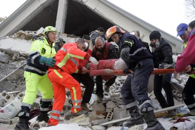 Firefighters carry a woman out of a crumbled home in the city of L'Aquila, after a strong earthquake rocked central Italy early Monday. Damage was reported as far as Rome, 70 miles away.  (Associated Press / The Spokesman-Review)
