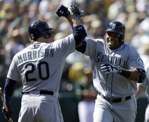Mariners' Nelson Cruz, right, celebrates with teammate Logan Morrison after hitting three-run home run. (Associated Press)
