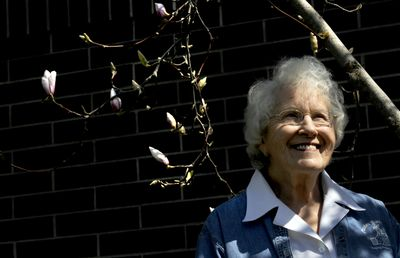 Jean Smart stands beneath a blooming magnolia tree at North Idaho College on  April 24. Smart has been a Master Gardener since 2000. She and her husband, Harold, have lived in North Idaho since 1993.   (Kathy Plonka / The Spokesman-Review)