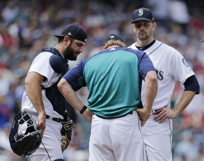 Seattle Mariners pitching coach Mel Stottlemyre, center, talks on the mound with starting pitcher James Paxton and David Freitas in the sixth inning just before giving up a home run to Colorado's Noel Cuevas on July 7 in Seattle. (John Froschauer / AP)