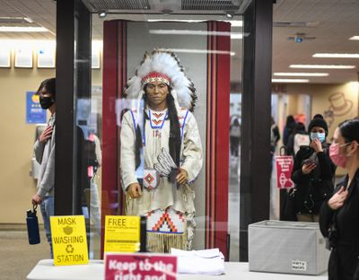 Students and a Spokane Public Schools administration member pause in the North Central High School hallway around the statue of a Native American during the Pledge of Allegiance on the first day of in-person classes on March 1, 2021. A state law signed Monday, April 26, 2021 will require North Central to change its mascot from the Indians.  (DAN PELLE/THE SPOKESMAN-REVIEW)