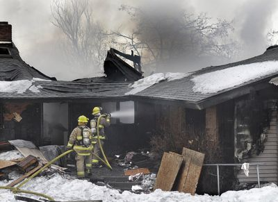 Fire District 8 firefighters work Wednesday to put out the second fire  at 4808 S. Dyer Road in two days.  (Christopher Anderson / The Spokesman-Review)