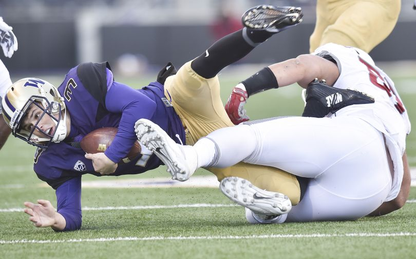 Washington quarterback Jake Browning (3) is brought down from a run by WSU during the first half of the Apple Cup on Friday, Nov 27, 2015, at Husky Stadium in Seattle, Wash. (Tyler Tjomsland / The Spokesman-Review)